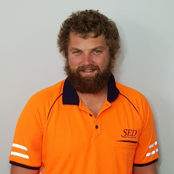 Male Employee wearing Orange uniform smiling at the camera