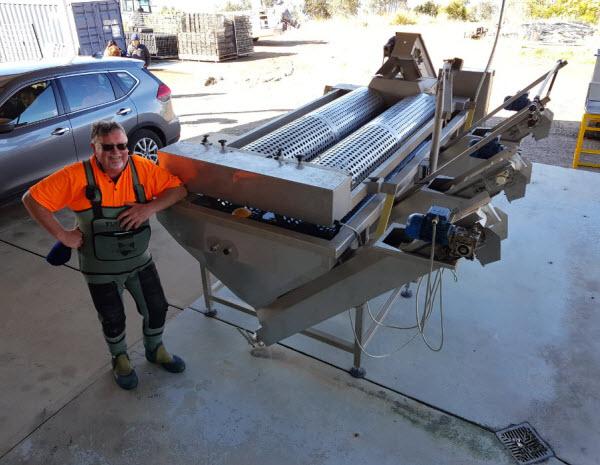 Man standing beside an equipment inside a warehouse